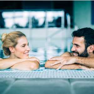 happy-attractive-couple-relaxing-in-swimming-pool-picture-id1097394840