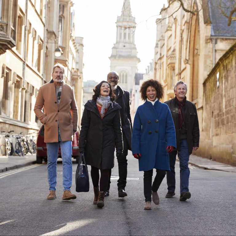 Group Of Mature Friends Walking Through City In Fall Together