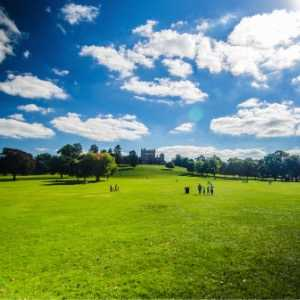 people-walking-at-wollaton-hall-on-a-sunny-day-picture-id454361495